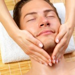 Portrait of happy man and hands giving face massage